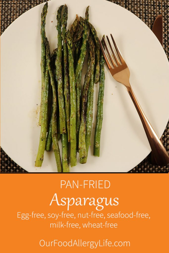 Pan-Fried Asparagus on a white plate with a copper fork next to it.